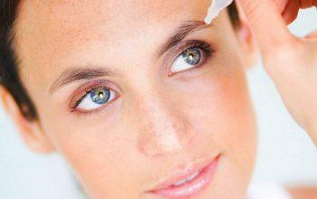mujer colocando gotas en su ojo