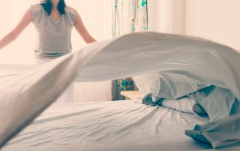mujer tendiendo cama